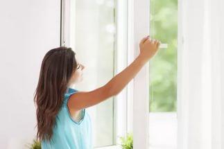 Девушка стоит у окна, микроклимат в квартире